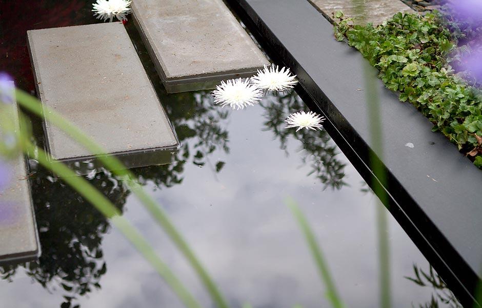 Spejlbassin med vand og trædefliser